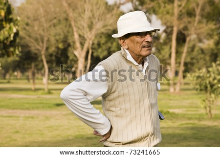 senior golfer playing golf on a sunny evening. - stock photo