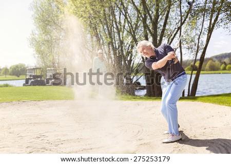 Senior golfer swinging golf club in sand bunker. - stock photo
