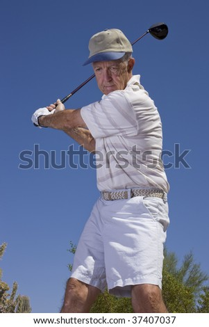 Senior golfer swinging the golf club on a summer day - stock photo