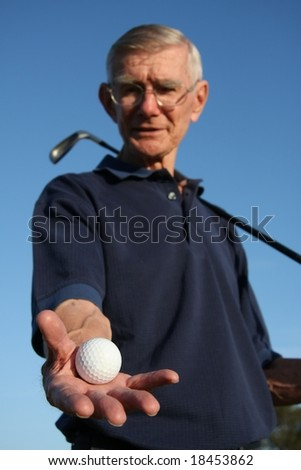 Senior golfer with ball in outstretched hand - stock photo