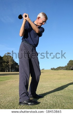 Senior golfer with driver club aiming at ball - stock photo