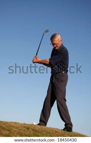 Senior golfing man about to strike the ball in the fairway - stock photo