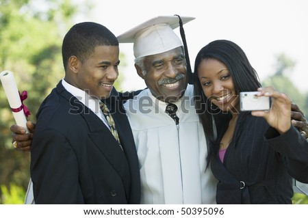 Senior graduate taking picture with grandchildren outside