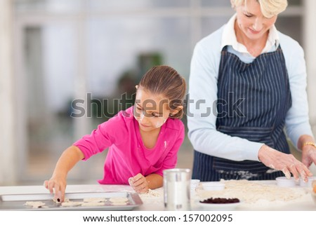 senior grandmother baking cookies with granddaughter in kitchen