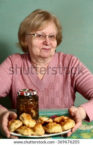 senior grannie with glasses with pies and mushrooms can close up portrait - stock photo