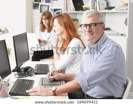 Senior graphic designer sitting at desk and working together with colleagues. Small business. - stock photo