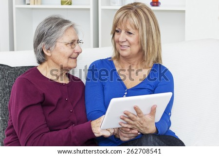 Senior gray haired woman sitting on  the sofa in the living room close to female nurse and  they together using a digital tablet .  - stock photo