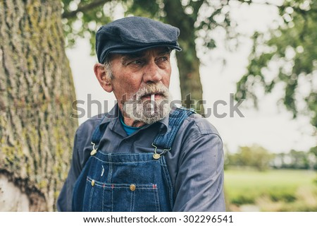 Senior grey-haired bearded country farmer standing smoking in his cloth cap and denim dungarees as he stares thoughtfully into the distance - stock photo