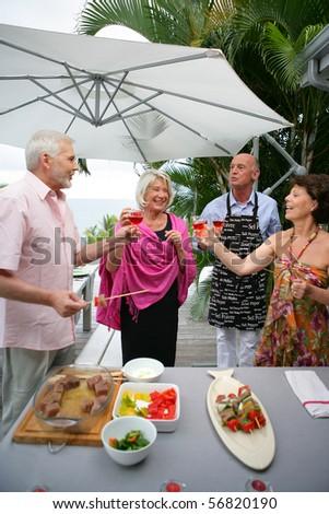 Senior group having a toast on a terrace - stock photo