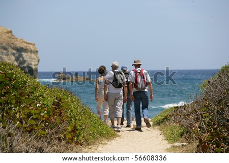 Senior group hiking at the seafront - stock photo