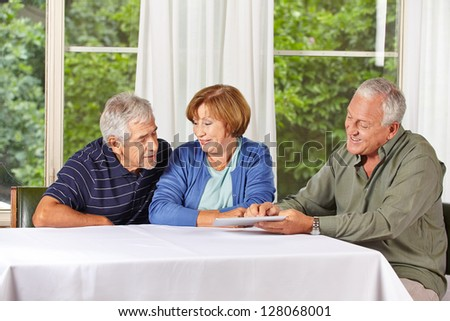 Senior group looking at touchscreen of a tablet PC computer - stock photo