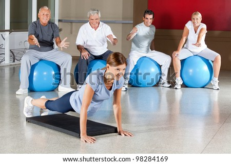 Senior group motivating woman in gym who does push ups