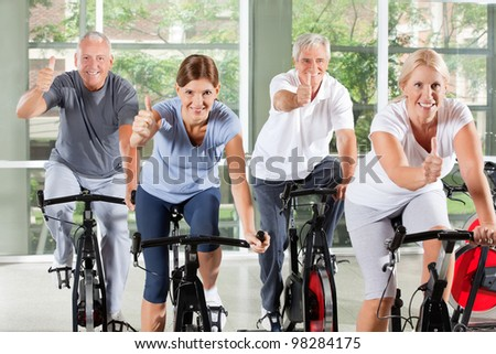 Senior group on bikes in gym holding thumbs up - stock photo