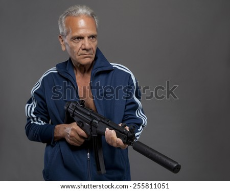 senior gunman shooter with rifle in front of grey background - stock photo