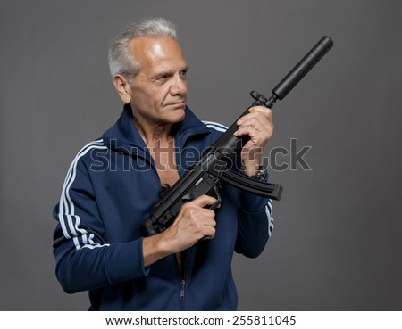 senior gunman shooter with rifle on grey background