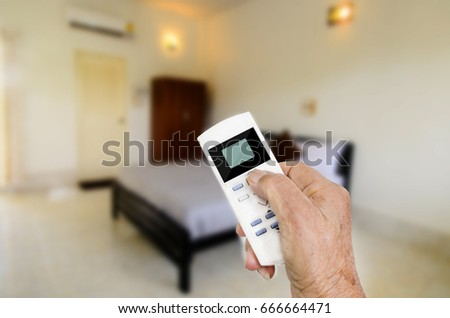 Senior hand holding remote control with blurry room background.  Modern lifestyle concept
