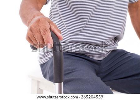 senior hand holding walking stick - stock photo