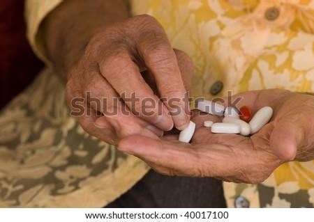 senior hand sorting through a handful of medications - stock photo