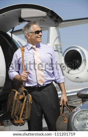Senior happy businessman standing by airplane with luggage at airfield - stock photo
