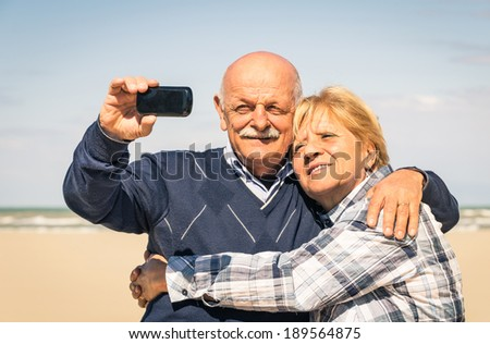 Senior happy couple taking a selfie at the beach during spring waiting for the summer - Concept of elderly and interaction with new technologies and trends - stock photo