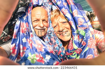Senior happy couple taking a selfie at the week clothes market traveling around the world - Concept of active elderly and interaction with new technologies and trends - stock photo
