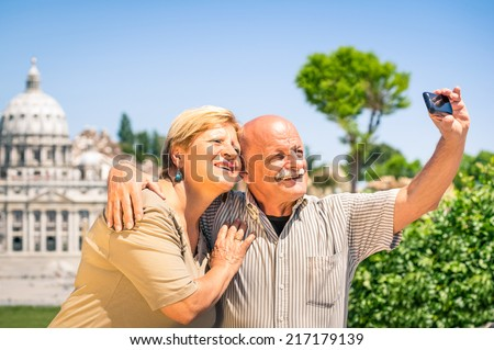 Senior happy couple taking a selfie photo picture near the basilca of St. Peter's in Vatican City in Rome - Concept of active elderly and interaction with new technologies and trends - stock photo