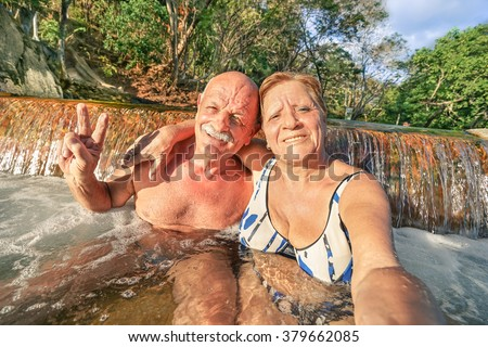 Senior happy couple taking selfie at Maquinit Hot Spring in Coron - Relax concept to Philippines wonders and active elderly traveling around the world - Warm afternoon color tones with tilted horizon - stock photo