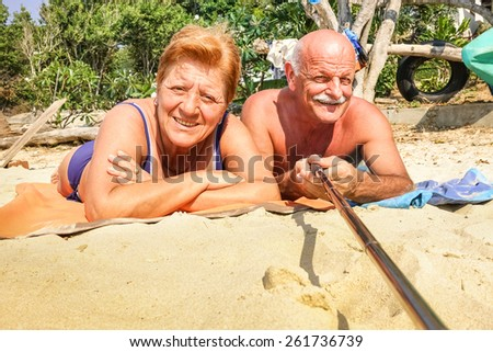 Senior happy couple taking selfie with stick in Thailand trip - Adventure concept of active elderly and fun around the world - Hot sunny day with real saturated light conditions - stock photo