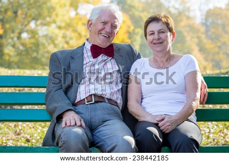 Senior happy marriage sitting on a park bench in sunny afternoon - stock photo