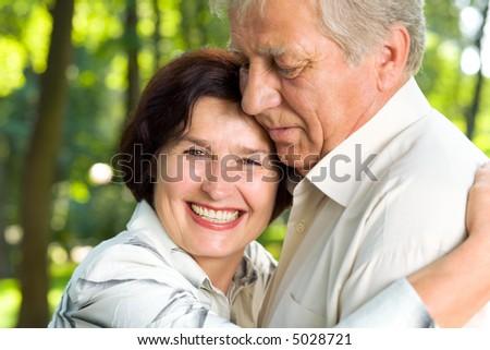 Senior happy smiling couple walking together outdoors - stock photo