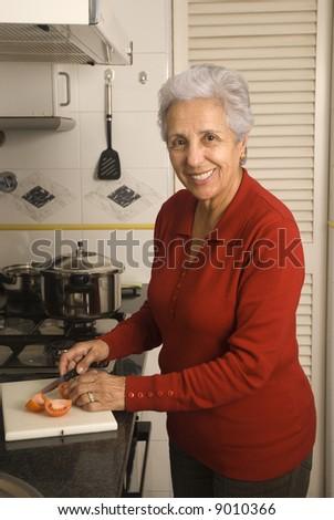 Senior happy woman cooking at kitchen - stock photo
