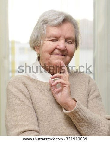 Senior happy woman in her home with window on background.