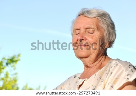 Senior happy woman on blue sky. MANY OTHER PHOTOS FROM THIS SERIES IN MY PORTFOLIO.  - stock photo