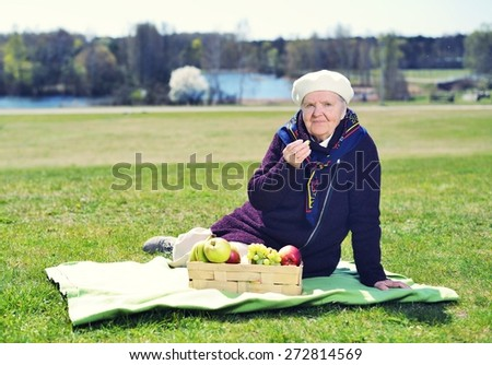 Senior happy woman sitting on a blanket on glade in the park. Healthy outdoor activities. Happy and smiling. MANY OTHER PHOTOS FROM THIS SERIES IN MY PORTFOLIO.  - stock photo