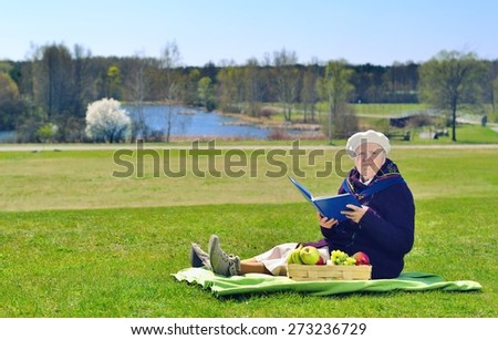 Senior happy woman sitting on a blanket on glade in the park. She is reading book. Healthy outdoor activities. Happy and smiling. MANY OTHER PHOTOS FROM THIS SERIES IN MY PORTFOLIO.  - stock photo