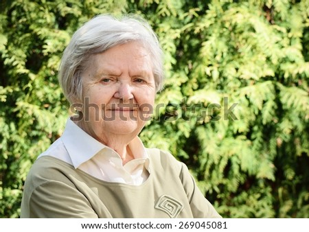Senior happy woman smiling in garden. MANY OTHER PHOTOS FROM THIS SERIES IN MY PORTFOLIO.  - stock photo