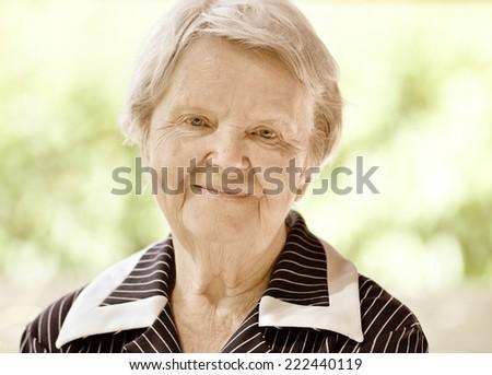 Senior happy woman smiling in garden. Vintage style. - stock photo