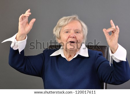 Senior happy woman with grey hairs against grey background. MANY OTHER PHOTOS WITH THIS SENIOR MODEL IN MY PORTFOLIO. - stock photo