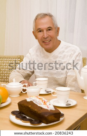 Senior has a breakfast with a cake - stock photo