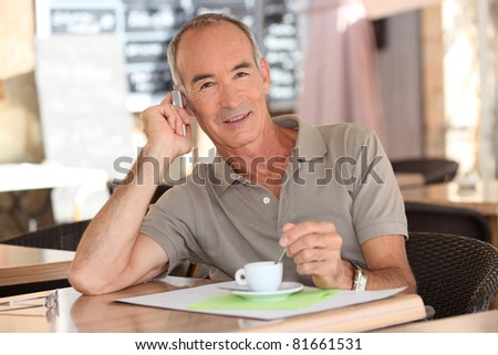 Senior having an espresso while talking on his cellphone - stock photo