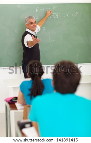 senior high school teacher teaching math in classroom - stock photo