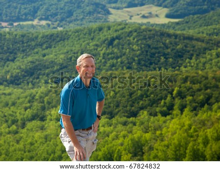 Senior hiker looks over valley in the Shenandoah on a climb of Old Rag - stock photo