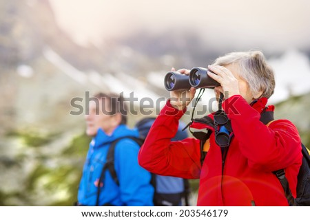 Senior hikers couple enjoying the landscape view with binoculars - stock photo