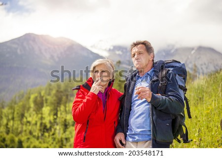Senior hikers couple smoking during the walk in the mountains - stock photo
