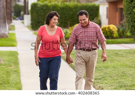 Senior Hispanic Couple Walking Along Sidewalk Together