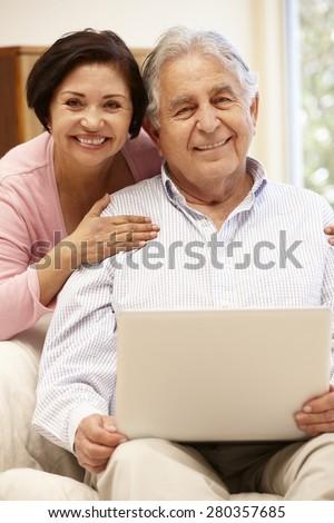 Senior Hispanic couple with laptop - stock photo