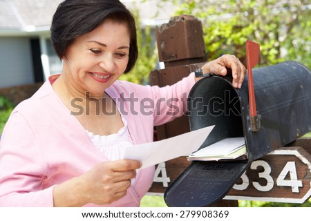 Senior Hispanic Woman Checking Mailbox - stock photo