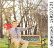 Senior holding flowers and taking selfie in park shot with tilt and shift lens - stock photo