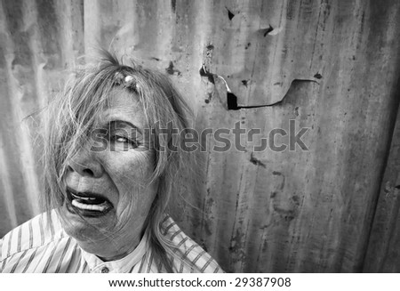 Senior homeless woman with too much makeup crying - stock photo
