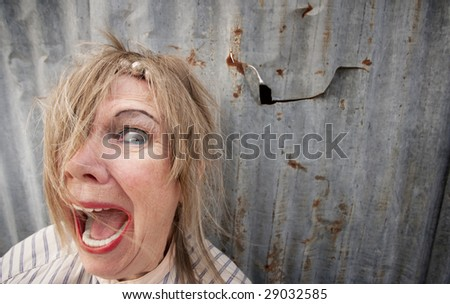 Senior homeless woman with too much makeup screaming - stock photo